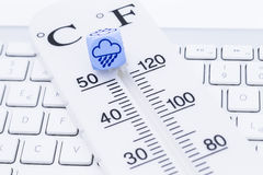 Weather forecast. Image shows a thermometer with cube on a keyboard Royalty Free Stock Image