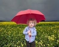 Weather forecast. Little blond boy under red umbrella Stock Photo
