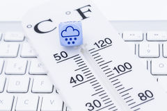 Weather forecast snow. Image shows a thermometer with cube on a keyboard Royalty Free Stock Image