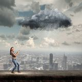 Weather forecast. Young woman in casual catching cloud with rope Stock Photography