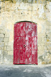 Weather red door in limestone building. Weather red door in old limestone building royalty free stock photo