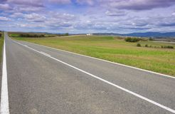 Weather, sky with clouds and straight road Royalty Free Stock Image