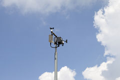 Weather station mast against blue cloudy sky Royalty Free Stock Images
