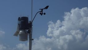 Weather station for meteorological forecast on blue clear sky background, anemometer, wind meter and direction sensors.