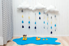 Weather symbols. Handmade room decoration clouds with rain drops, puddle, child yellow rubber boots and ducks. Autumn weather concept Royalty Free Stock Image