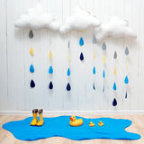 Weather symbols. Handmade room decoration clouds with rain drops, puddle, child yellow rubber boots and ducks Royalty Free Stock Photo