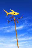 Weather Vane. Golden weather vane with shark figure over cloudy blue sky royalty free stock photography
