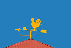 Weather vane. A yellow weather vane in a blue sky royalty free stock photos