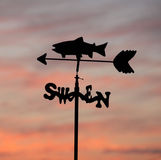 Weather Vane. A weather vane points Southwest with a red sky in the background stock photos