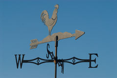 Weather vane. Rooster against clear blue skies stock images