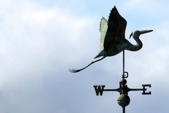 Weather Vane. A green colored egret weather vane against a blue sky facing in an easterly direction stock photo