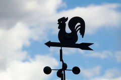 Weather vane. On a backgrounds a cloudy sky royalty free stock images
