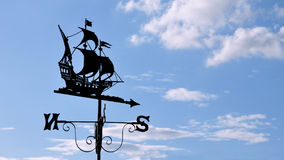 Weather Vane. Antique Ship Weather Vane against a Blue Cloudy Sky stock photos