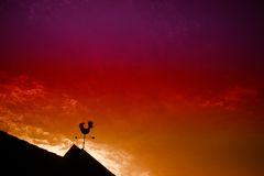 Weather vane. Chicken weather vane with a beautiful sky and sunset in the background stock photos
