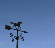Weather Vane. Rooftop weather vane against a clear blue sky royalty free stock image