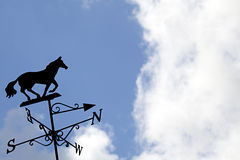 Weather vane against a blue sky with clouds Royalty Free Stock Images