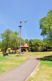 Weather Vane. Along a paved path in a manicured park setting with generic outdoor shelter under a blue sky stock images