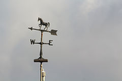 Weather vane with arrow and horse. Weather vane with arrow, horse, W and E on cloudy sky background stock image