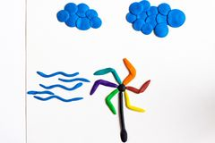 The weather vane with blades of various bright colors is spinning from a strong wind. Weathervane, wind and clouds above them are made of plasticine on a white royalty free stock image