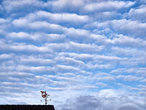 Weather vane and a cloudy sky. Weather vane on a roof on a cloudy morning stock photography