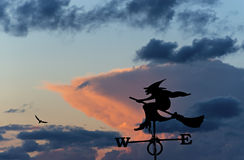 Weather vane at cloudy sky. Weather vane with witch on broomstick on sky background stock photography