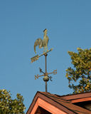 Weather vane bird. Vintage weather vane bird on the red roof above blue sky stock images