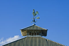 Weather vane and cupola. A rooster weather vane and a cupola on the roof Royalty Free Stock Images