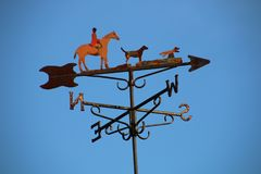 Weather Vane English hunter team. Close up of metal weather vane indicating all four cardinal point with figurines of English rider in red coat on brown horse stock photography