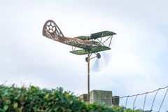 Weather vane in form of an old rusty biplane, at a 3/4 view close-up, with propellers moving fast. Weather vane in form of an old rusty biplane at a 3-4 view royalty free stock photography