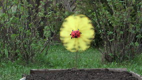 Weather-vane. The weather vane in the form of a yellow flower rotates on a wind stock video