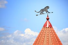 Weather vane with the image of a lion. Against the background of the blue sky royalty free stock photos