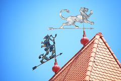 Weather vane with the image of a lion. Against the background of the blue sky royalty free stock images