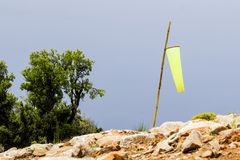 Weather vane on the mountainside and against the blue sky.  royalty free stock photography