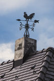 Weather vane on the roof. Of the house royalty free stock photo