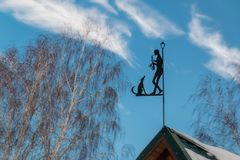 Weather vane on a roof. Stylish weather vane on a roof in the form of the musician with a saxophone and a dog Stock Photo