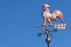 Weather Vane Rooster. A copper rooster weather vane against a clear blue sky stock images
