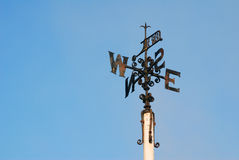 Weather vane. Rusty weather vane on top of pole in cloudless blue sky royalty free stock image