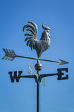 Weather vane showing direction of wind against clear blue sky, vertical. Weather vane, wind vane, weathercock, showing direction of the wind against clear blue Stock Image