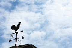 Weather Vane Silhouette against cloudy sky. A weather vane, wind vane, or weathercock is an instrument for showing the direction of the wind. It is typically stock images