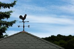 Weather Vane Silhouette against cloudy sky. A weather vane, wind vane, or weathercock is an instrument for showing the direction of the wind. It is typically stock photos