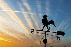 Weather vane at sunset. Weather vane is instrument showing direction of wind - typically used as an architectural ornament to the highest point of a building stock images