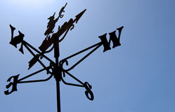 Weather Vane. Witch on a broomstick weather vane silhouette against blue sky on rooftop royalty free stock photography