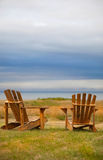 Weathered Adirondack Chairs. A Pair Of Weathered Adirondack Chairs Looking Out Over The The Ocean Stock Images