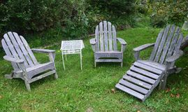 Weathered Adirondack chairs on green lawn Stock Photos