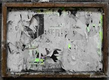 A weathered advertising frame with layers of torn posters Royalty Free Stock Photos