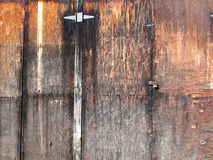 Weathered Age Old rustic Plywood. An old weathered garage door decorated with old sheets of plywood and metal part accents royalty free stock image