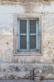 Weathered and Ancient Maltese shuttered window , blue. Traditional Maltese blue wooden window, with shutters and fading paint.  Crumbling wall, shot straight-on Royalty Free Stock Images