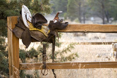 Weathered Antique Saddle on Fence stock photo