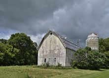 Weathered Barn and Silo under a cloudy sky stock photos