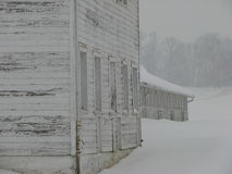 Weathered barn on a snowy cloudy winter day Royalty Free Stock Image